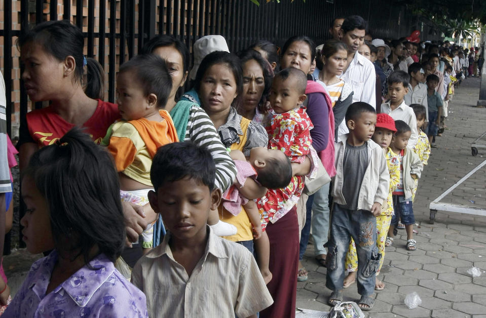 Cambodian villagers line up to wait for a medical check-up outside Kuntha Bopha children's hospital in Phnom Penh, Cambodia, Wednesday, July 11, 2012. The enterovirus 71 strain, or EV-71, raised fears earlier this week after it was detected in some lab samples taken after 52 of 59 Cambodian children died suddenly from a mystery illness that sparked international alarm. Health officials are still investigating, but say the virus is likely to blame. (AP Photo/Heng Sinith)