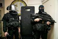 French BRI police commandos pose with the bullet-riddled Ramses shield used in the raid (AFP/Kenzo TRIBOUILLARD)