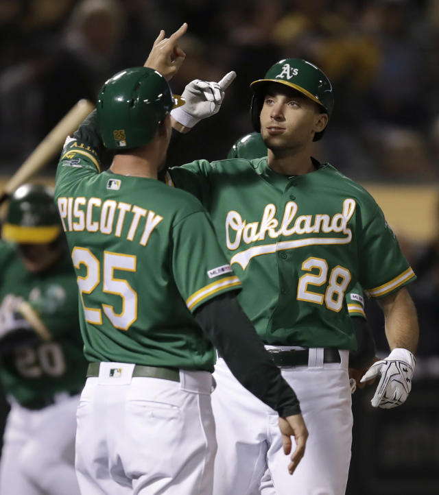 Oakland Athletics' Matt Olson, right, celebrates with Stephen Piscotty (25) after hitting a three-run home run off Seattle Mariners' Wade LeBlanc during the fourth inning of a baseball game Friday, May 24, 2019, in Oakland, Calif. (AP Photo/Ben Margot)