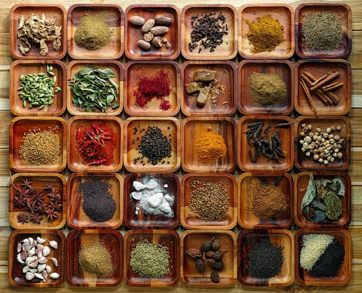 Common Indian herbs and spice ingredients on wooden trays.