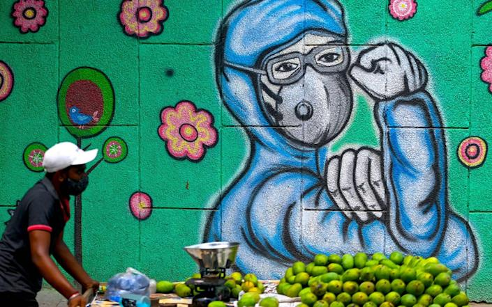 In New Delhi, India, a fruit vendor pulls his cart as he walks past a wall mural depicting a frontline Covid-19 health worker - MONEY SHARMA/AFP via Getty Images