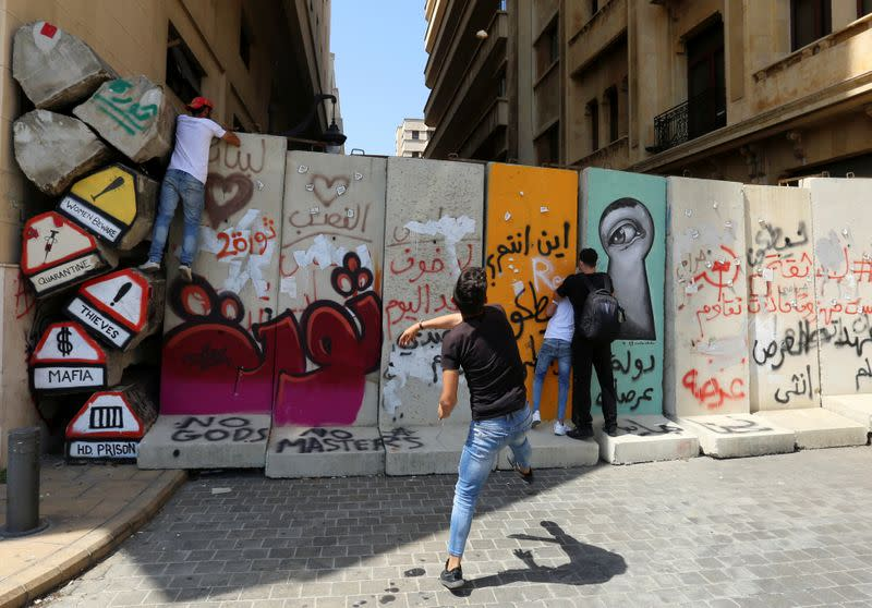 A demonstrator throws a stone during a protest against the government performance and worsening economic conditions, in Beirut