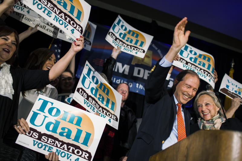 FILE - In this Nov. 4, 2014, file photo, Sen. Tom Udall, D-N.M., waives to supporters with his wife, Jill Cooper Udall, right, at the Double Tree hotel after being re-elected as one of New Mexico's Senators in Albuquerque, N.M. Udall says he will not seek re-election in 2020 in a move that opens up a secure Democratic seat to competition. He announced the end of his 20-year political career in Washington in a statement on Monday, March 25, 2019. (AP Photo/Craig Fritz, File)