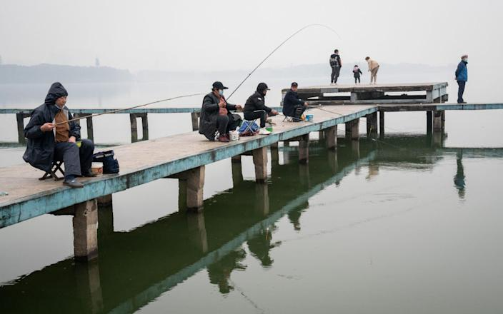 People fish in Donghu Lake in Wuhan, - Yan Cong for the Telegraph