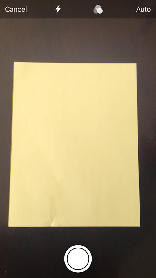 """<p>Once you hit """"Scan Documents,"""" a camera screen will appear. Point your phone camera at your document. It should automatically locate the document and highlight it in yellow (this can sometimes take a few tries at first - don't worry!). Once the document you want to scan is highlighted completely in yellow, it will automatically capture the document image or you can also tap the bottom white icon to do this. In my case, my document was easily detected and automatically scanned and saved.</p>"""