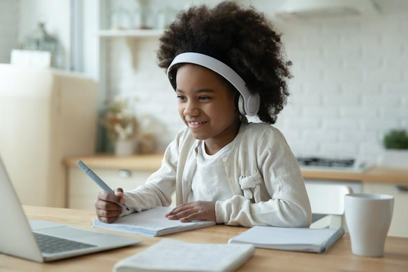 A child wearing headphones at a laptop.
