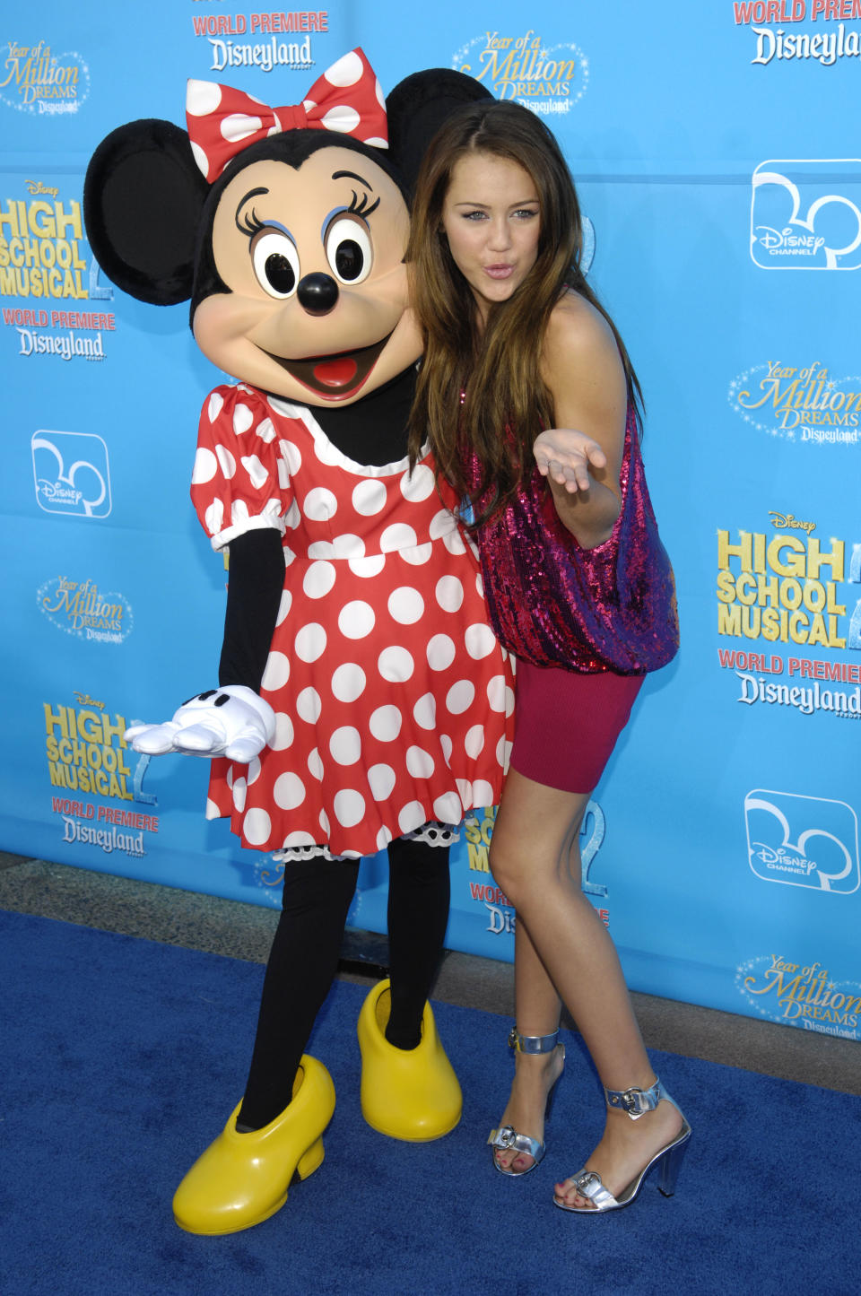 """Actress Miley Cyrus, right, is seen with character Minnie Mouse during arrivals to the premiere of """"High School Musical 2"""" at Disneyland in Anaheim, Calif., Tuesday, Aug. 14, 2007. (AP Photo/Chris Pizzello)"""