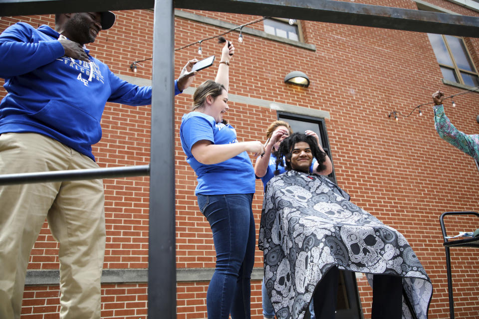 """In this image provided by Gregg Gelmis, friends and family publicly cut Kieran Moïse's hair, which was then donated to the nonprofit Children With Hair Loss, Saturday, May 29, 2021, in Huntsville, Ala. Moïse also launched a fundraiser through St. Jude Children's Research Hospital in memory of classmate Josh Quist, who died from cancer. So far their charity, """"Kieran's Curls for Cancer,"""" has raised $35,000. (Courtesy of Gregg Gelmis via AP)"""