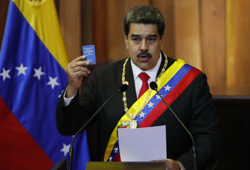 Venezuela's President Nicolas Maduro holds up a small copy of the constitution as he speaks during his swearing-in ceremony at the Supreme Court in Caracas, Venezuela, Thursday, Jan. 10, 2019. Maduro was sworn in to a second term amid international calls for him to step down and a devastating economic crisis. (AP Photo/Ariana Cubillos)