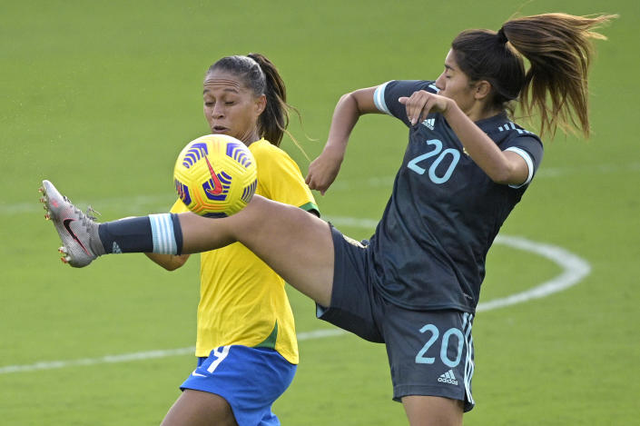 Brazil defender Rafaelle, left, and Argentina midfielder Daiana Falfan (20) battle for the ball during the second half of a SheBelieves Cup women's soccer match, Thursday, Feb. 18, 2021, in Orlando, Fla. (AP Photo/Phelan M. Ebenhack)