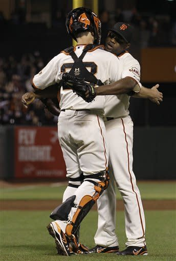 San Francisco Giants pitcher Santiago Casilla, right, celebrates with catcher Buster Posey after the final out of the ninth inning of a baseball game against the Colorado Rockies in San Francisco, Monday, May 14, 2012. The Giants won 3-2. (AP Photo/Jeff Chiu)