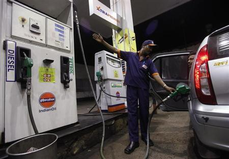 A worker fills a car with petrol as he gestures towards the fuel barometer for the passenger to check, at a fuel station in Kolkata September 15, 2011. REUTERS/Rupak De Chowdhuri