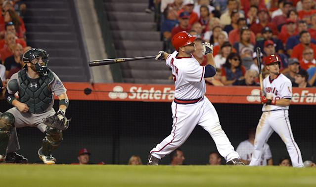 Los Angeles Angels' Chris Iannetta watches his two-run home run, between Oakland Athletics catcher Derek Norris, left, and Angels' Gordon Beckham during the fifth inning of a baseball game, Friday, Aug. 29, 2014, in Anaheim, Calif. (AP Photo/Mark J. Terrill)