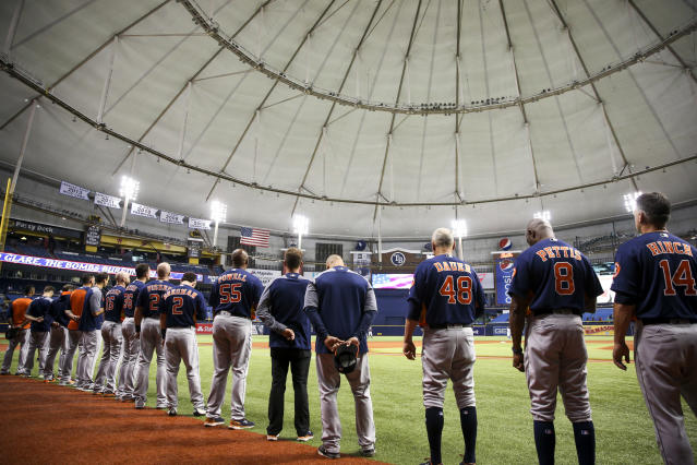 The Houston Astros stand for the national anthem before a baseball against the Texas Rangers in St. Petersburg, Fla. (AP)