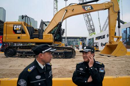 FILE PHOTO: Security guards stand in front of heavy machinery of Caterpillar at Bauma China, the International Trade Fair for Construction Machinery in Shanghai, China November 27, 2018. REUTERS/Aly Song