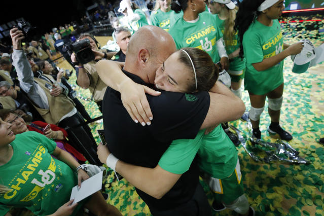 Oregon's Sabrina Ionescu, right, embraces head coach Kelly Graves after defeating Stanford in an NCAA college basketball game in the final of the Pac-12 women's tournament Sunday, March 8, 2020, in Las Vegas. (AP Photo/John Locher)
