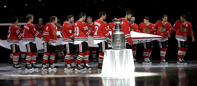 The Chicago Blackhawks carry out the Stanley Cup Championship banner past the Stanley Cup during a ceremony before an NHL hockey game between the Blackhawks and the Washington Capitals Tuesday, Oct. 1, 2013, in Chicago. (AP Photo/Nam Y. Huh)