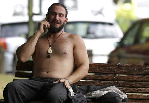 A tearful man reacts as speaks on a phone close to one of the Christchurch mosques (AP)