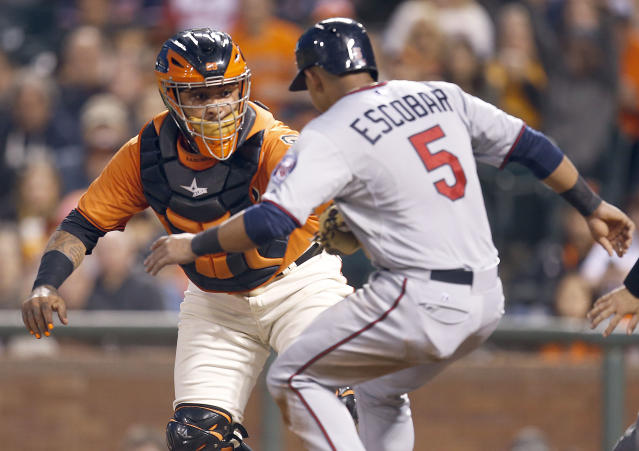 San Francisco Giants catcher Hector Sanchez (29) tags out Minnesota Twins' Eduardo Escobar (5) at home plate in the third inning of a baseball game Friday, May 23, 2014, in San Francisco. (AP Photo/Tony Avelar)