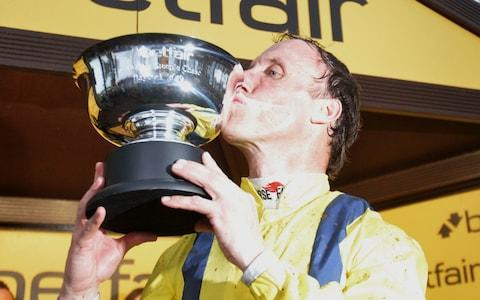 Robbie Power poses with the trophy after winning the Betfair Steeple Chase on Lostintranslation - Credit: PA