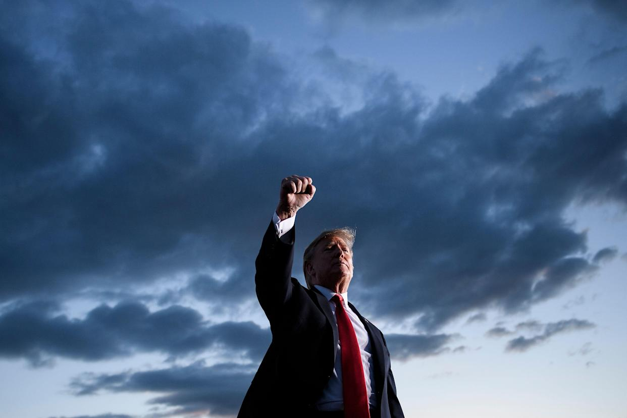President Trump holds up his fist as he leaves a Pennsylvania rally in May. (Photo by Brendan Smialowski/AFP/Getty Images)
