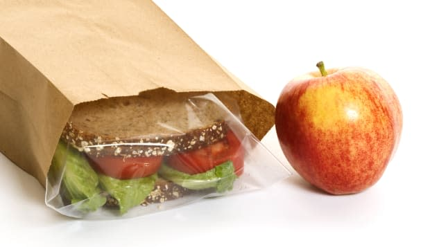Sandwich in a bag with an apple on the side