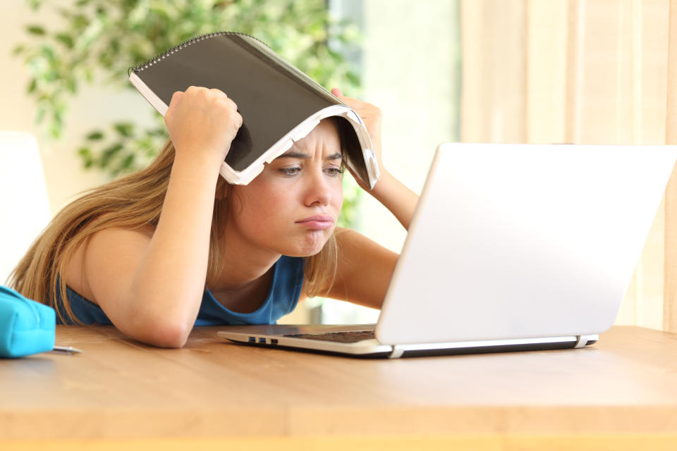 Bored student doing homework on line with a laptop blowing with a notebook on the head in a table at home