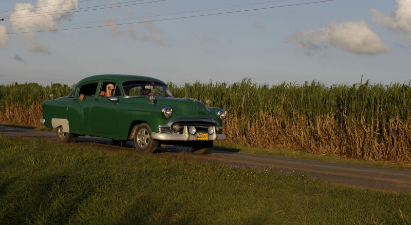 In this Sept. 8, 2012 photo, people drive a classic American car past a sugar cane field in Camaguey, Cuba.  Just two years ago, Cuba's sugar industry was on its knees after the worst harvest in more than a century. Now Cuba's signature industry is showing signs of life. With world market prices rebounding, sugar is suddenly more profitable, and a reorganization of the sector could offer a blueprint for how to lift up the rest of the island's economy.  (AP Photo/Franklin Reyes)