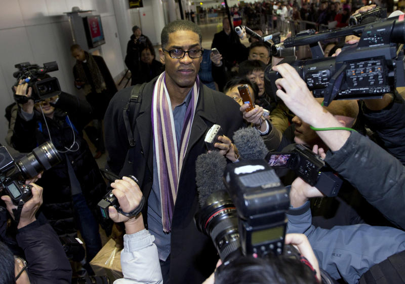 Former NBA basketball star Charles D. Smith, center, is mobbed by journalists upon arrival at the Beijing Capital International Airport in Beijing from Pyongyang, North Korea, Friday, Jan. 10, 2014. A squad of former basketball stars led by Dennis Rodman had a friendly game with North Korean basketball players in Pyongyang. (AP Photo/Andy Wong)