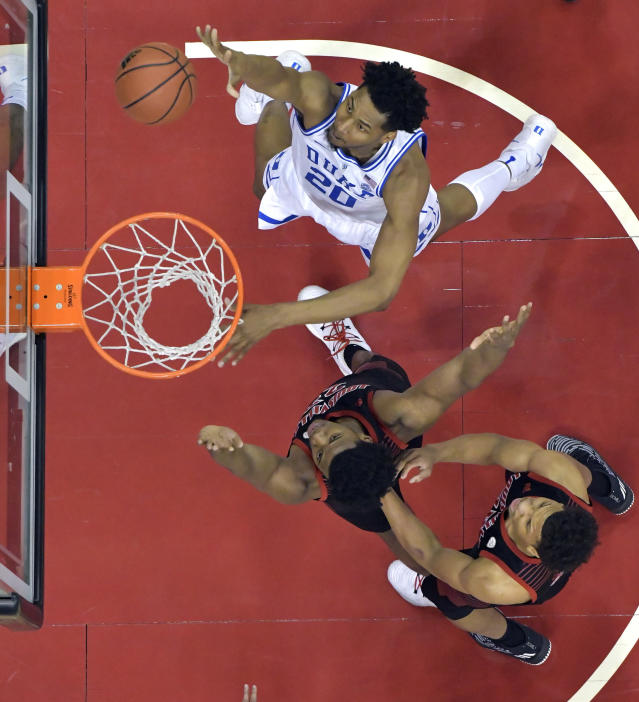 Duke center Marques Bolden (20) shoots next to Louisville center Steven Enoch, center, and forward Dwayne Sutton during the first half of an NCAA college basketball game in Louisville, Ky., Tuesday, Feb. 12, 2019. Duke won 71-69. (AP Photo/Timothy D. Easley)