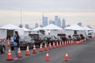 Philadelphia Medical Reserve Corps volunteer Emma Ewing, left, a sophomore at Temple University, directs cars at the city's coronavirus testing site next to Citizens Bank Park in South Philadelphia on Friday, March 20, 2020. The site, which opened Friday afternoon, is the first city-run drive-through location where people can be swabbed to determine if they have the coronavirus. At the time of opening, it was only for people with symptoms who are over 50 and healthcare workers with symptoms. (Tim Tai/The Philadelphia Inquirer via AP)