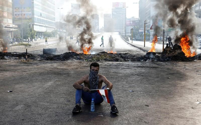 A demonstrator sits near burning tires as he holds a Lebanese flag during a protest over the deteriorating economic situation, in Dora