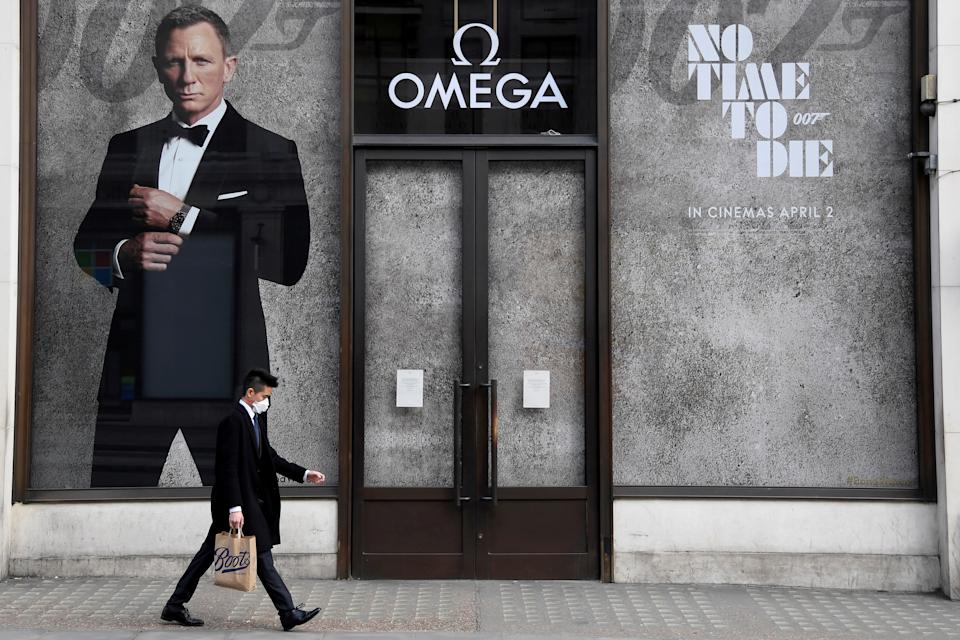 A man walks past a shop promoting the new James Bond film No Time To Die in London on 20 March 2020 as the coronavirus spread. It had originally been due for release on 2 April 2020