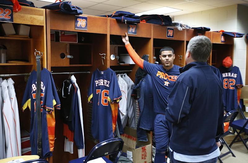 Houston Astros' Rene Garcia talks with general manager Jeff Luhnow in the clubhouse before a spring training baseball workout, Saturday, Feb. 15, 2014, in Kissimmee, Fla. (AP Photo/Alex Brandon)