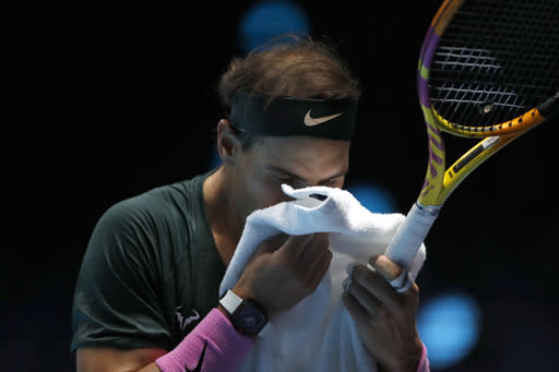 Rafael Nadal of Spain wipes his face during his singles tennis match against Dominic Thiem of Austria at the ATP World Finals tennis tournament at the O2 arena in London, Tuesday, Nov. 17, 2020. (AP Photo/Frank Augstein)