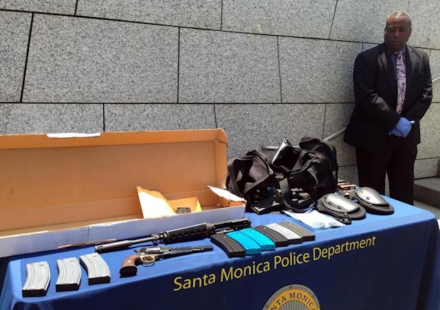 An unidentified law enforcement official stands Saturday June 8, 2013, by weapons and other evidence recovered from the gunman in Friday's deadly shooting rampage that left four people dead, in Santa Monica, Calif. The gunman killed his father and brother at their home and another man at nearby Santa Monica College, authorities said. (AP Photo/Tami Abdollah)