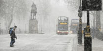<p>Pedestrians cross Whitehall as snow falls in London.A warning of heavy snow showers is in place for east England, London and the south-east, and the Midlands until 10am. (AP Photo/Alastair Grant) </p>