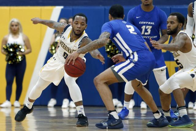 In this Thursday, Feb. 27, 2020 photo, Merrimack College guard Juvaris Hayes, left, reaches in to force a steal from Central Connecticut guard Myles Baker (2) during the second half of an NCAA college basketball game in North Andover, Mass. The Warriors have been one of the biggest surprises in college basketball, winning more games than any other first-year Division I program in history. (AP Photo/Mary Schwalm)