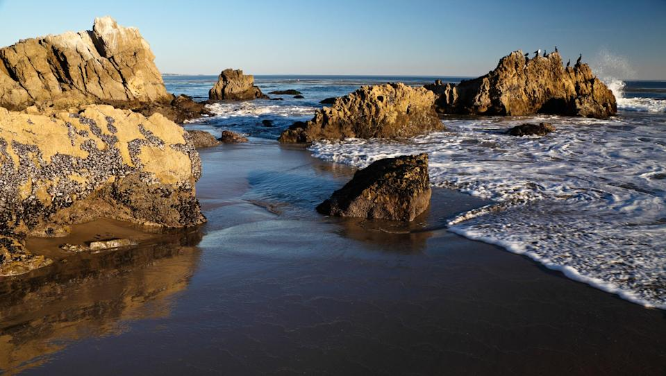 """<p><strong>Give us the wide-angle view: what kind of beach are we talking about?</strong><br> Leo Carrillo State Park (named for the actor and conservationist) is an ecologically diverse spot with rocky crags jutting into the ocean, <a href=""""https://www.cntraveler.com/story/best-hikes-in-malibu?mbid=synd_yahoo_rss"""" rel=""""nofollow noopener"""" target=""""_blank"""" data-ylk=""""slk:Malibu mountains to hike"""" class=""""link rapid-noclick-resp"""">Malibu mountains to hike</a>, and pristine water with rich tidepools. Set on 1.5 miles of perfect beach, it's a paradise for surfers, swimmers, beach loungers, windsurfers, fishing enthusiasts, and curious explorers of coastal caves. There is a campground here, shaded by giant sycamore trees, and a number of hiking trails that offer expansive views of the ocean.</p> <p><strong>How accessible is it?</strong><br> Parking at Leo Carrillo is easy and costs from $3 (for an hour) to $12 (for a full day). There's a path that goes underneath the Pacific Coast Highway from the beach to the campsites, of which there are 135. They range in price from $45 for a standard site, to $60 for one with an electrical hook-up, to $225 for a large group campsite.</p> <p><strong>If we didn't bring it, can we still get what we need here?</strong> <br> The Leo Carrillo State Park Campground Beach Store sells everything you might have forgotten to take on your camping trip, including snacks and outdoor apparel.</p> <p><strong>How's the actual beach stuff—sand and surf?</strong><br> The water at Leo Carrillo is accommodating for any type of visitor. Small swells are perfect for bodysurfing or beginner surfers, but not too choppy, so kayaking is also an option. The ocean is blue and clear—ideal for diving or snorkeling.</p> <p><strong>Can we go barefoot?</strong><br> Parts of the beach are rocky areas that become tide pools full of crabs and starfish during low tide. For the most part, though, the beach is sandy and amenable to throwing down a beach blanket and lazing out """