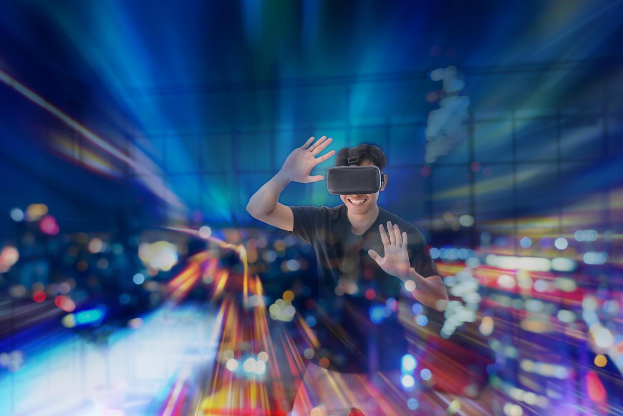 Young Asian man getting experience with VR virtual reality headset or 3D glasses in living room at home. technology, gaming, entertainment concept