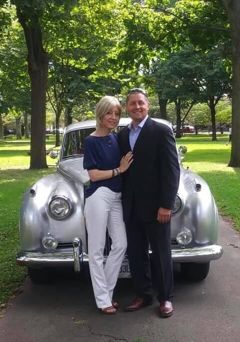 man and woman standing in front of rolls royce car