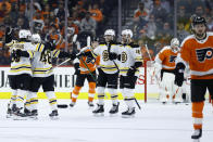 Boston Bruins' Matt Grzelcyk (48) celebrates with teammates after scoring a goal during the second period of an NHL hockey game against the Philadelphia Flyers, Tuesday, March 10, 2020, in Philadelphia. (AP Photo/Matt Slocum)