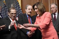 House Speaker Nancy Pelosi of Calif., second from right, gives pens to, from left, House Judiciary Committee Chairman Rep. Jerrold Nadler, D-N.Y., House Foreign Affairs Committee Chairman Rep. Eliot Engel, D-N.Y., and House Ways and Means Committee Chairman Rep. Richard Neal, D-Mass., after she signed the resolution to transmit the two articles of impeachment against President Donald Trump to the Senate for trial on Capitol Hill in Washington, Wednesday, Jan. 15, 2020. The two articles of impeachment against Trump are for abuse of power and obstruction of Congress. (AP Photo/Susan Walsh)