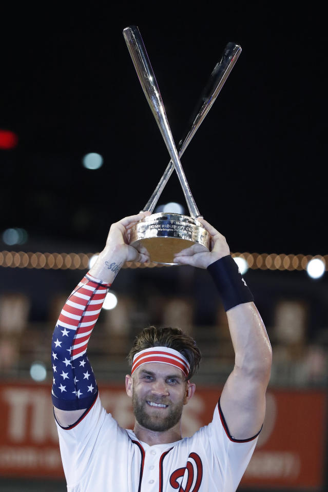 Washington Nationals Bryce Harper holds up the trophy after winning the the Major League Baseball Home Run Derby, Monday, July 16, 2018, in Washington. (AP Photo/Alex Brandon)