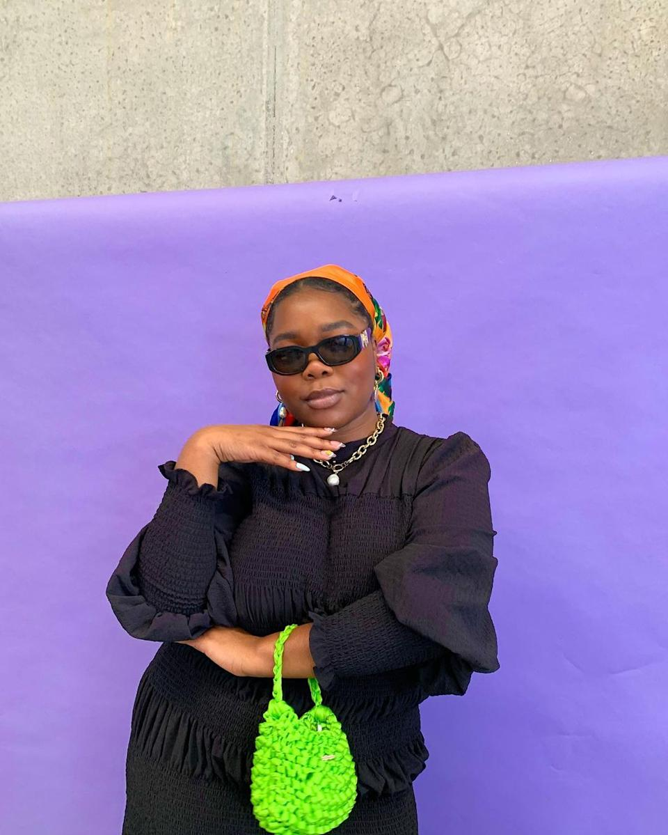 Lillian Ahenkan wearing a black outfit and an orange head scarf in front of a purple wall. Photo: Instagram/flex.mami.