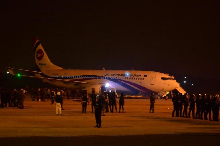 Bangladeshi security personnel stand guard near the hijacked Dubai-bound plane. Officials say the would-be hijacker was carrying a toy gun