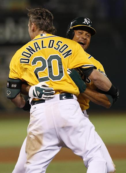Oakland Athletics' Josh Donaldson (20) celebrates with teammate Coco Crisp after hitting a walk-off single against the Los Angeles Angels during the ninth inning of a baseball game, Tuesday, Sept. 17, 2013, in Oakland, Calif. The Athletics beat the Angels 2-1. (AP Photo/George Nikitin)