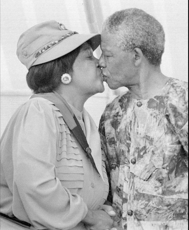 <p>President Nelson Mandela, right, kisses his wife, Winnie Mandela, at a rally in Cape Town in early 1993. Divorce proceedings between the couple began in Johannesburg's Rand Supreme Court on March 18, 1996, with President Mandela accusing his wife of adultery. (Photo: Benny Gool/AP) </p>