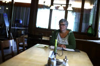 In this photo taken Friday, May 1, 2020 brewery daughter Sabine Detter sits on her accounting documentation in her 120 year old family brewery and traditional Bavarian restaurant in Altoetting, Germany. The 'Graminger Weissbraeu' brewery, which has been in the same family for a century, is preparing to welcome guests back to its restaurant for the first time in two months — with new rules and fears for the future. (AP Photo/Matthias Schrader)