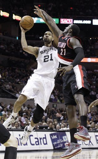 San Antonio Spurs' Tim Duncan, left, drives in front of Portland Trail Blazers' J.J. Hickson during the first quarter of an NBA basketball game, Monday, April 23, 2012, in San Antonio. (AP Photo/Eric Gay)